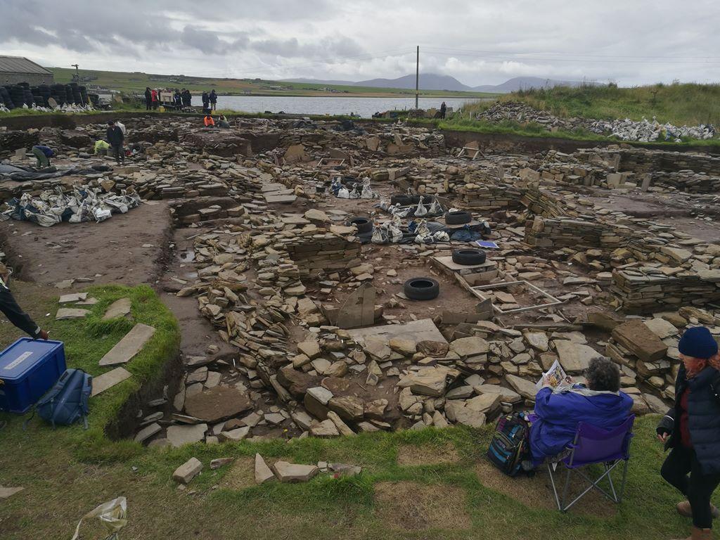 """2. kép: Lázasan folyik a munka a Ness of Brodgar lelőhelyen, a kép hátterében pedig a """"régészet turistái""""."""