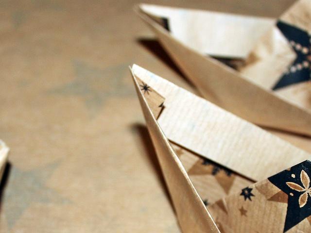 Papírforgó és papírhajó az ünnepi asztalon