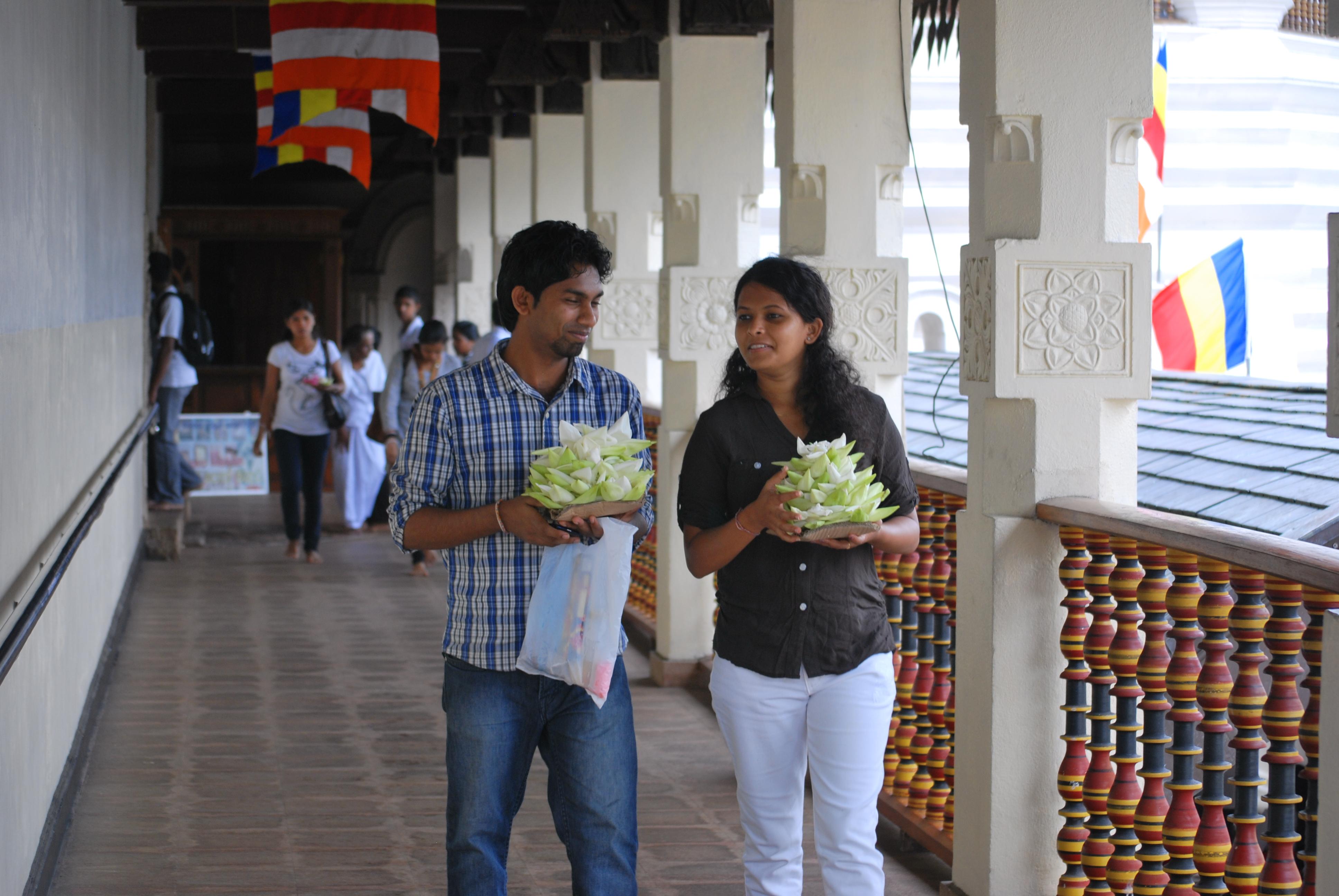 Buddhista hívek lótuszvirággal Kandyben, a fog templomában