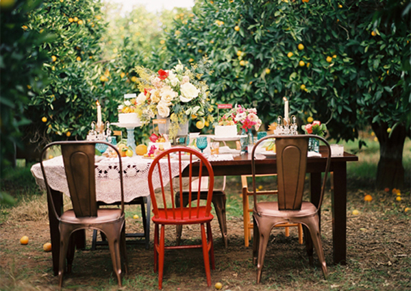 orchard-party-with-vintage-hankies-and-mismatched-chairs-and-table.jpg