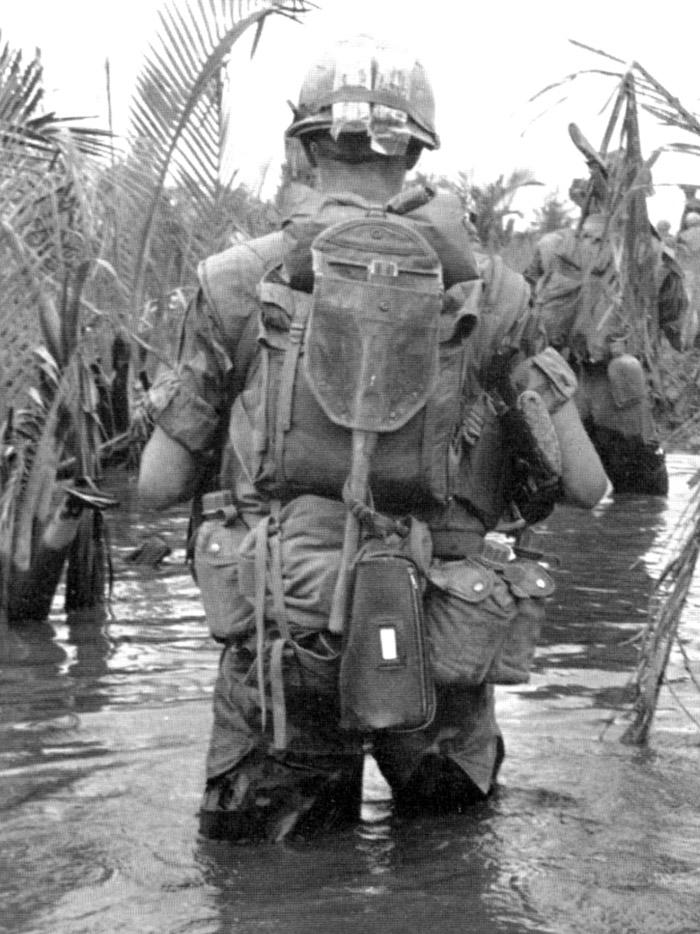 Tengerészgyalogos szerelvény. A vászon málhazsák alatt M1961-es kenyérzsákot visel, mely felett egy civil tisztálkodó készlet tokja lóg. A sisakhuzat pántja alatt kötszercsomagok figyelnek.