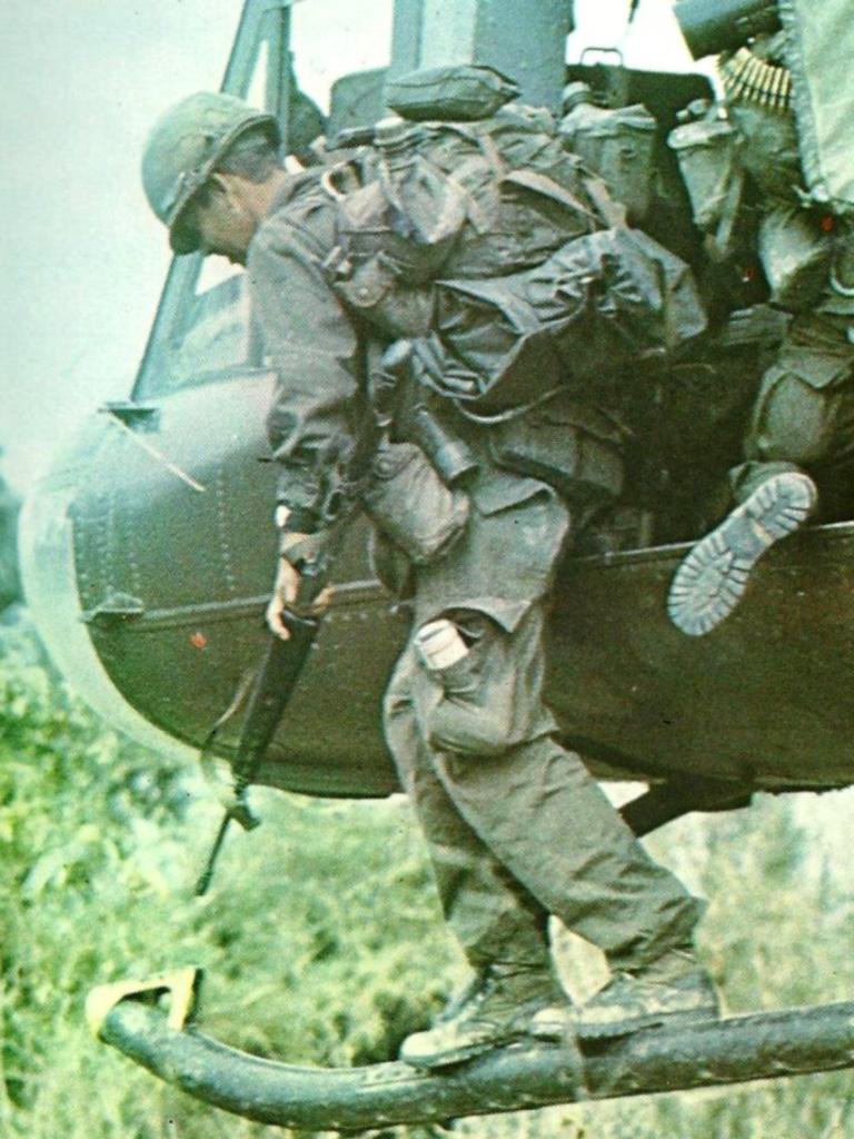A leszállásra készülő katona hátizsákján külsőleg rögzített ponchóbélés és pótkulacsok láthatók. Bal nadrágzsebéből pedig egy italosdoboz vagy gyümölcskonzerv kandikál ki.