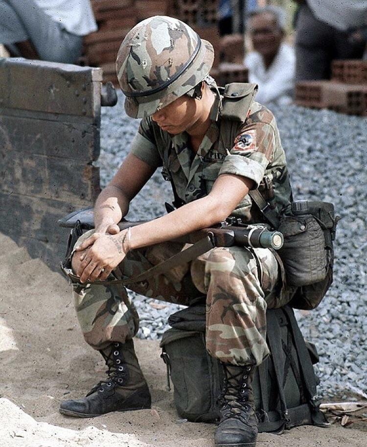 Dél-vietnámi ejtőernyős várakozik VKH-hátizsákján ülve. ERDL-mintás álcaruhát és dzsungelbakancsot visel, illetve M1956-os vászon szerelvényt, azonban kulacstokja már a késői műszálas változat. Vállán jól látható a légideszant-hadosztály hímzett jelvénye. M-79-esének csövébe farral előrefelé egy 40 mm-es gránátot dugott, 'készenléti jelleggel'.