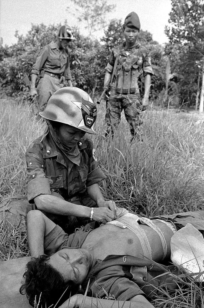 Elsősegély-nyújtás. A háttérben álló barettes katonán jól látható a kínai és észak-vietnámi tártartó mintájára készült, de már az M-3 géppisztoly hosszú táraihoz kialakított mellény, ahogy maga a fegyver is.