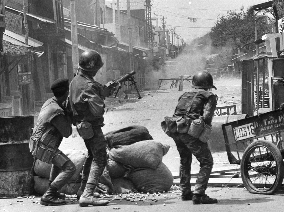 Katonák és rendőrök tüzelnek az ellenség felé a Tet-offenzíva saigoni harcai során. A bal oldalon látható alak átalakított málhamellényén vagy zubbonyán két sorban sorakoznak a tártartó zsebek.