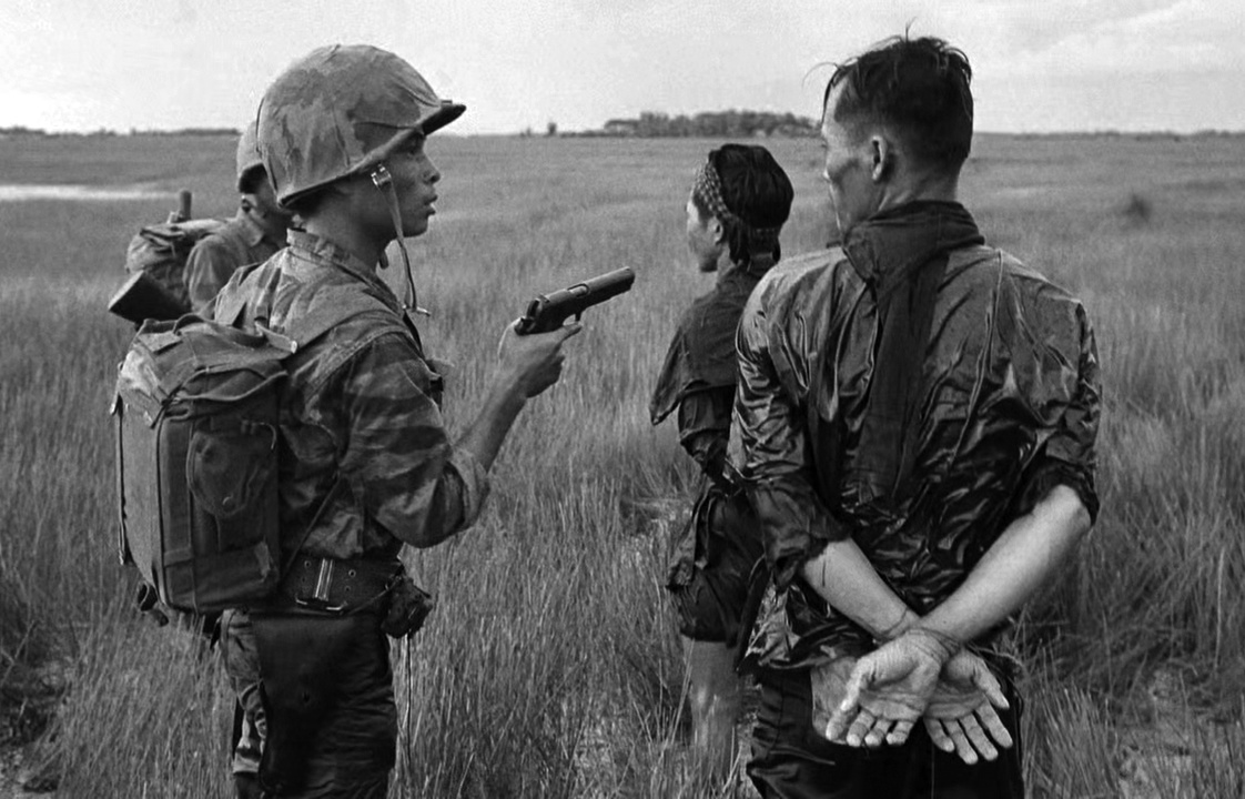 Tengerészgyalogosok foglyokat őriznek. A bal oldalon álló tiszt M1945-ös kenyérzsákot visel. Szerelvényén viszonylag kevés holmi látható.