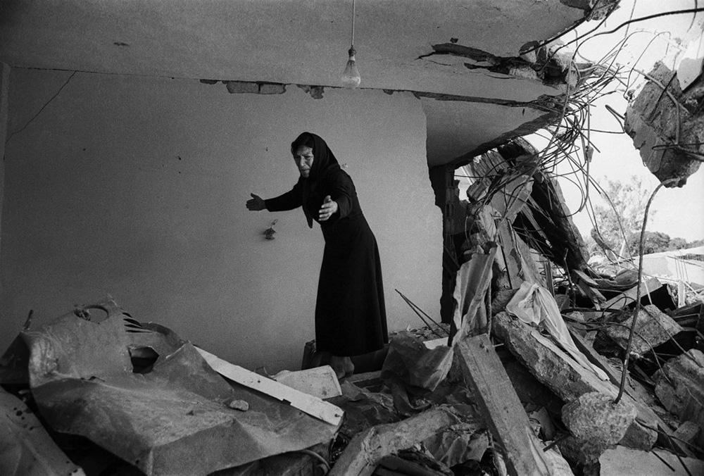 Palesztin asszony tér vissza romba dőlt otthonába. Bejrút, 1982.