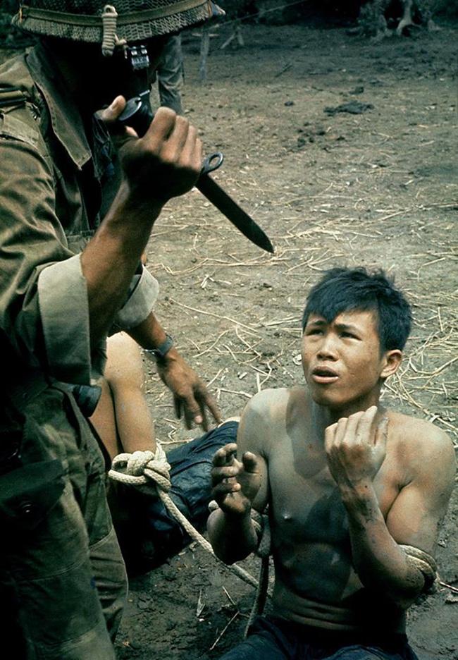 Dél-vietnámi katona vietkong foglyát fenyegeti