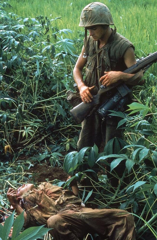 Tengerészgyalogos egy észak-vietnámi katona holtteste felett