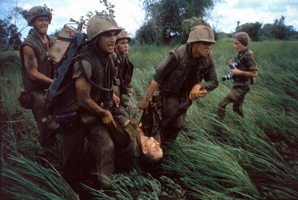 Tengerészgyalogosok viszik sebesült bajtársukat a helikopter felé a 484-es magaslatért vívott csata után. Jobb oldalon, a háttérben Catherine Leroy, a híres francia fényképész látható, akiről külön cikkben írtam