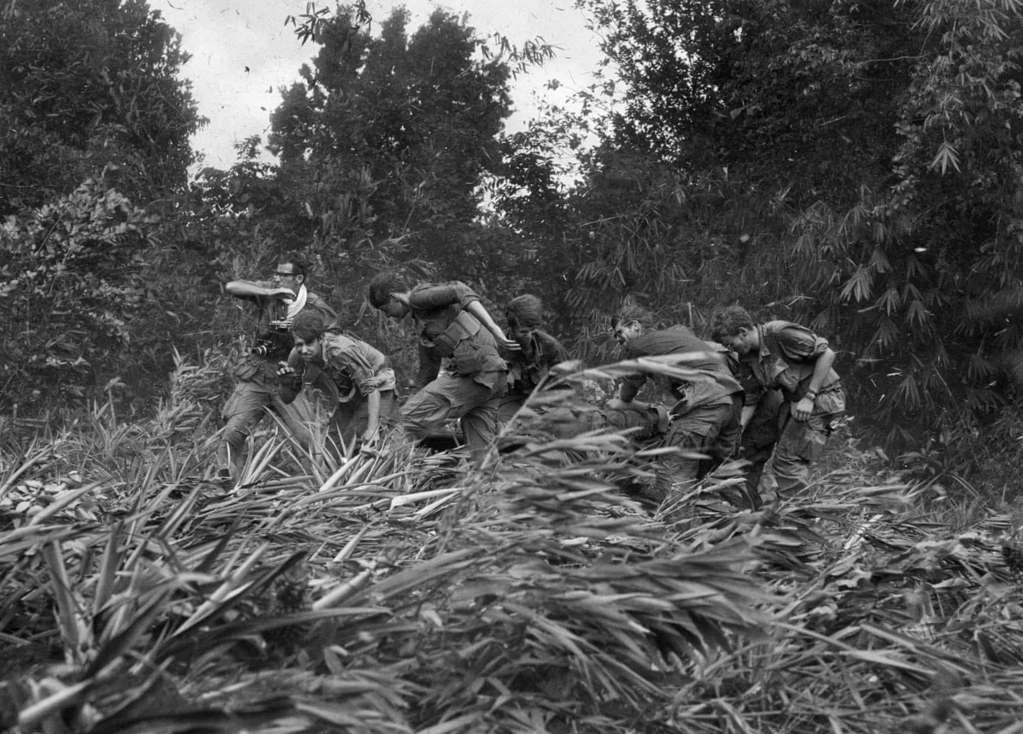 Burrows (a bal szélen, nyakában fehér törölközővel) katonáknak segédkezik sebesült bajtársuk kiemelésénél az 1970-es kambodzsai behatolás során
