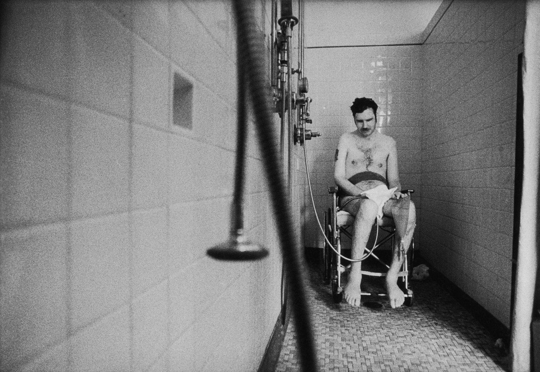 A megbénult Marke Dumpert, aki őrvezetőként szolgált a tengerészgyalogságnál, magatehetetlenül vár a tusolóban, hogy az ápolók megszárítsák.