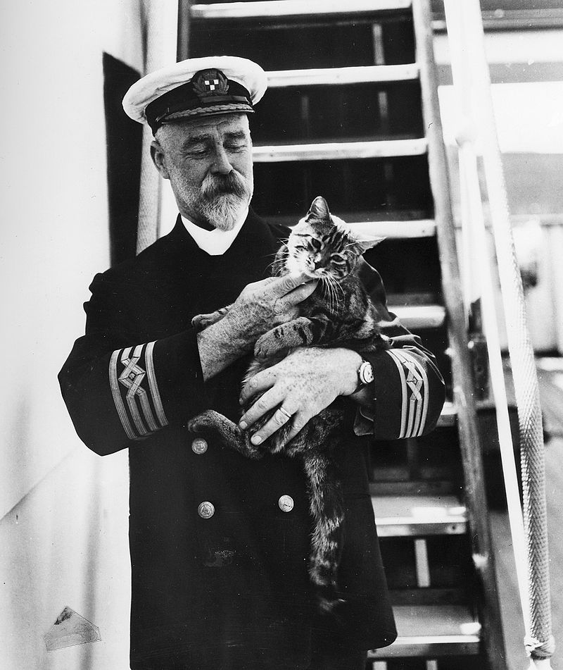 captain_a_j_hailey_in_uniform_with_a_cat_on_the_first_c_p_r_m_s_empress_of_canada.jpg