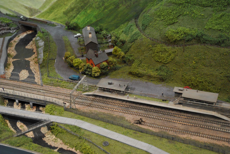 Az állomás félúton fekszik Sheffield és Manchester között, 1954-ben lett villamosítva a vonal, 1981-ben pedig bezárva. A terepasztal készítője ennek kívánt emléket állítani. Az állomásépület szintén egyedi tervezés.