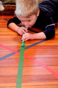 """Különböző cikk-cakkban ragasztott """"pályákon"""" kell végigfújni a pom-pom-ot.<br />Forrás: http://handsonaswegrow.com/fun-kid-activity-lines-of-colored-tape/<br />"""