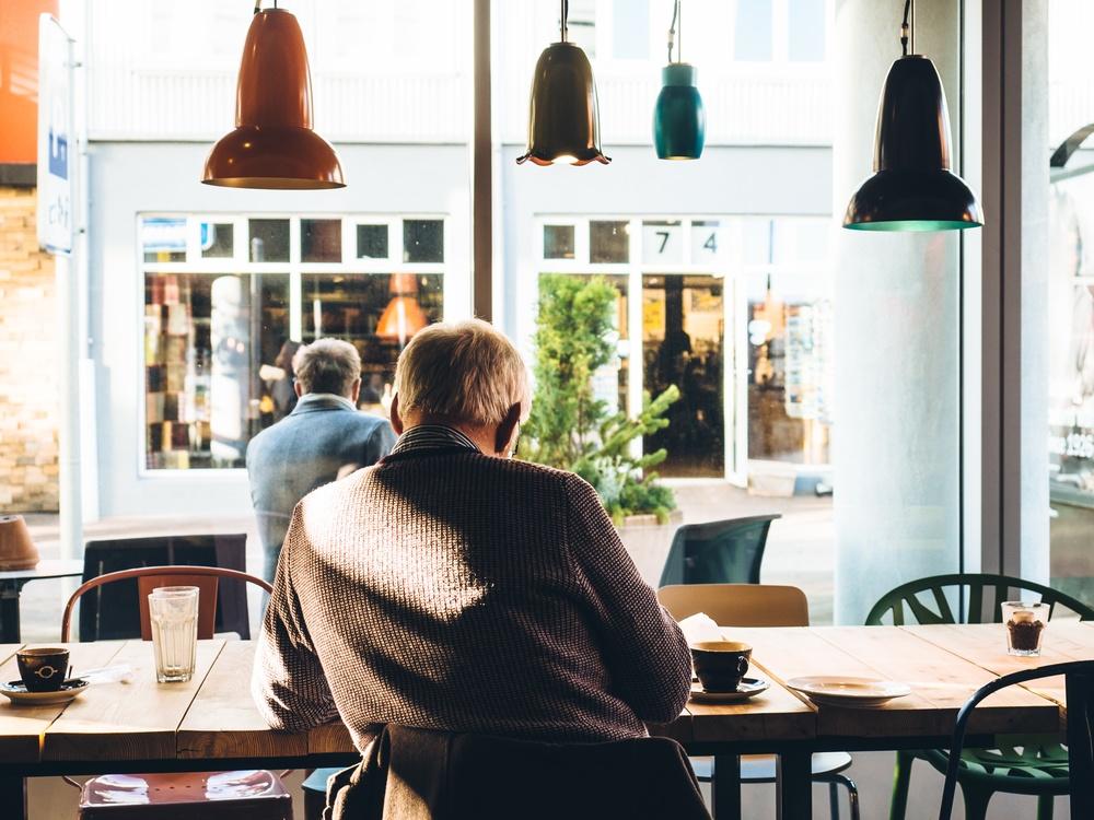 elderly_man_working_in_cafe.jpeg