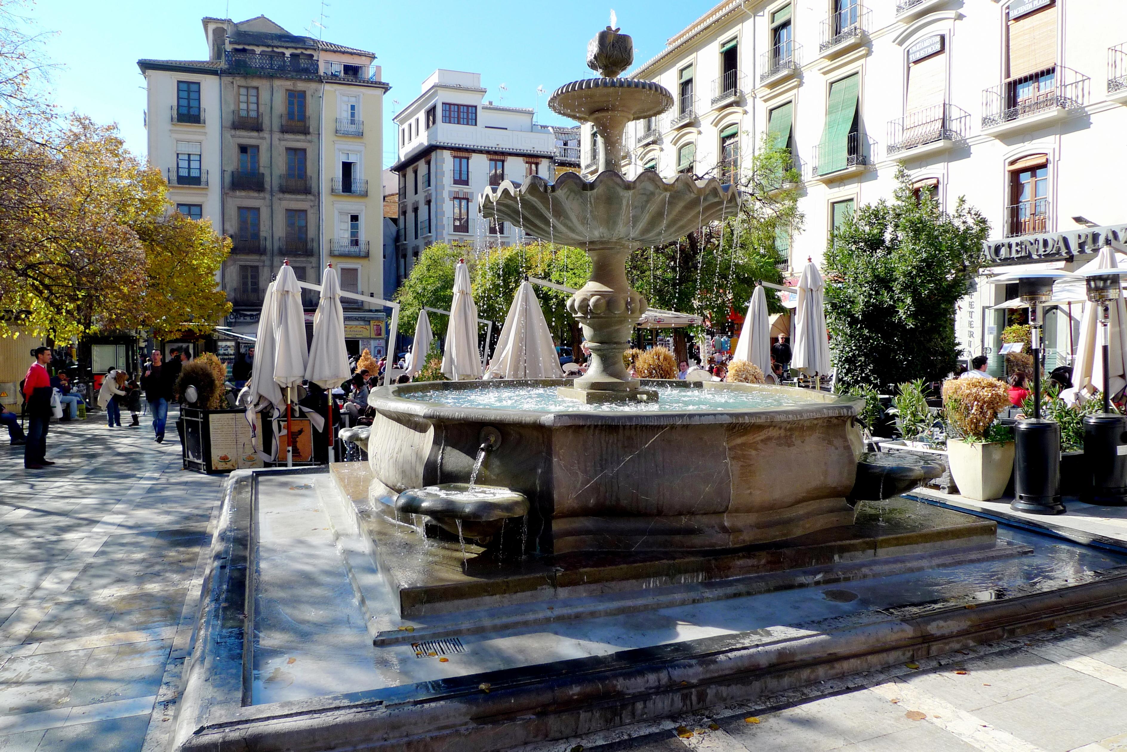 """A Plaza Nueva nagyon közel volt a panzióhoz, ez amolyan központi tér-féle, három városrész találkozik itt, az Albaicín, a régi zsidó negyed, a """"Realejo"""", és a központi városrész, az """"El Centro"""". Innen indul az Alhambrába vezető utca, állandóan teli van élettel, nyüzsögnek a turisták és a helyiek, utcai zenészek flamencot játszanak (hiszen a flamenco* Andalúziában született), hangulatos éttermek kínálnak pihenést és felfrissülést a tikkadt látogatónak, egy pár perces sétával eljutni a Darrohoz, és a Plaza Isabel Catolica is csak egy ugrás, úgyhogy a tér igazi turistamágnes. <br />* https://hu.wikipedia.org/wiki/Flamenco<br /><br />"""