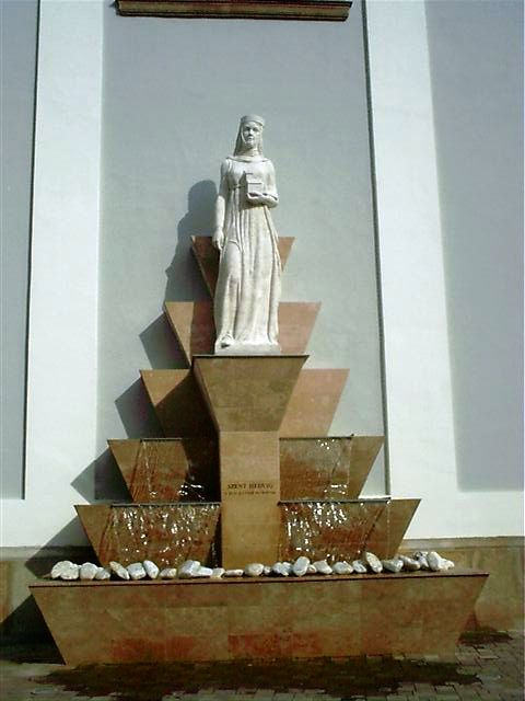 A Fehérek templomának oldalhomlokzatán áll Szent Hedvig szobra. <br /><br />Nagy Lajos magyar-lengyel király legkisebb leánya 1373-ban született . Szent Erzsébethez hasonlóan ő is a szegények, a betegek, az árvák és az özvegyek istápolója lett. Vagyonát, örökségét a szegények között osztotta szét és alapítványt hozott létre a krakkói egyetem részére. Fiatalon, 26 éves korában, 1399-ben hunyt el Krakkóban. <br /><br />Néhány éve a közelmúltban szentté avatott legendás lengyel királynő lett a Dunakanyar védőszentje.<br />Horváth Tibor alkotása<br />