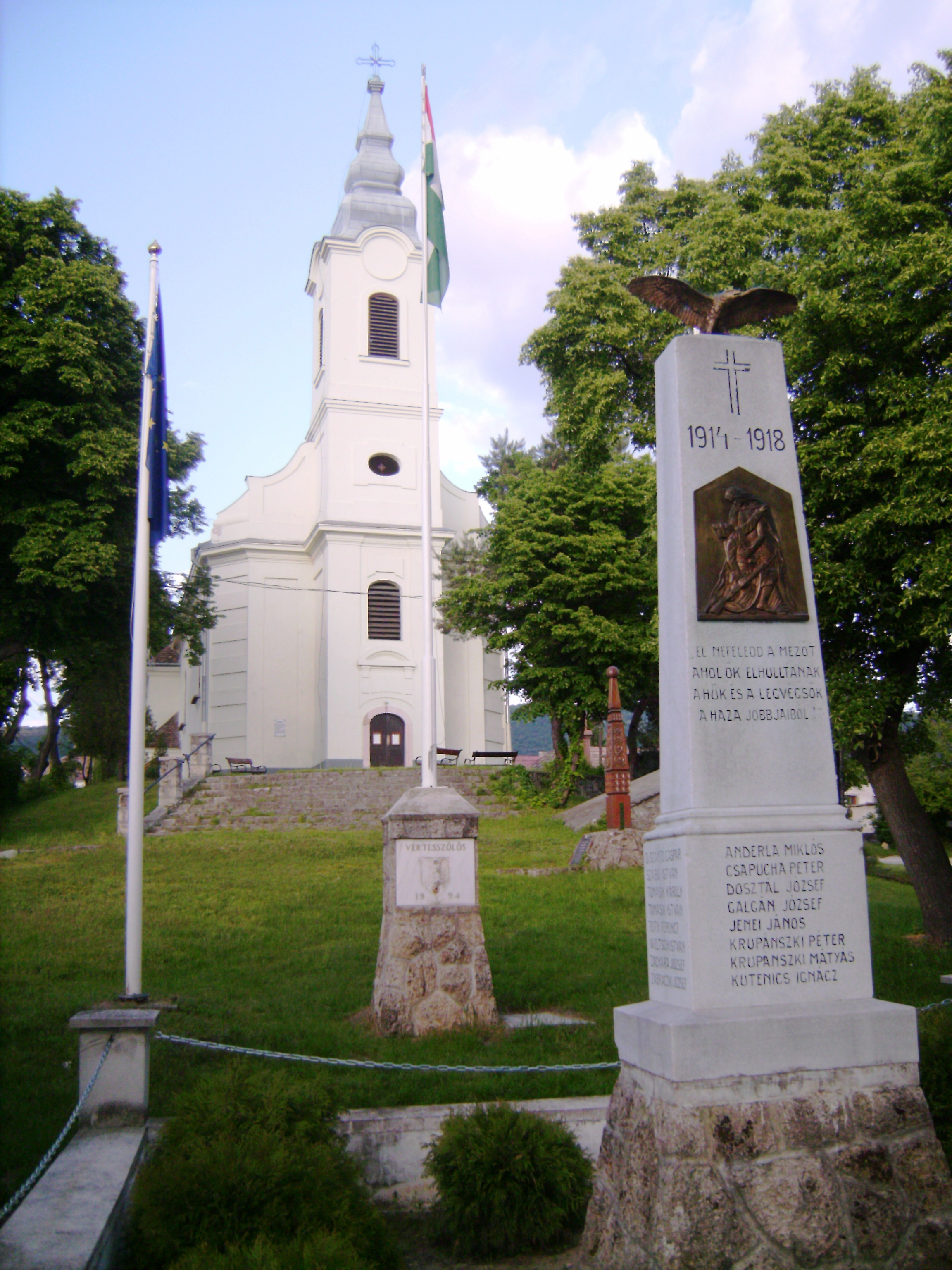 Előtte kicsit eklektikusan mindenféle emlékművek. Az előtérben egy hagyományos I. világháborús, mögötte kopjafa az 1848-49-es forradalom és szabadságharc emlékére, és egy szolid zászlótartó 1994-es dátummal, ekkor a település 770 éves volt.